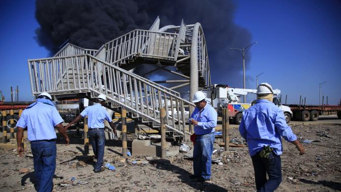 Rescue workers stand in front of damaged pedestrian bridge after a explosion in the Amuay refinery near Punto Fijo, Venezuela, Sunday, Aug. 26, 2012. Venezuelans who live next to the country's biggest oil refinery said they smelled a strong odor of sulfur hours before a gas leak ignited in an explosion on Saturday that killed at least 39 people and injured more than 80. (AP Photo/Ariana Cubillos)