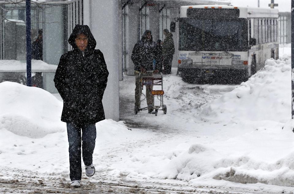 People walk in the snow in Buffalo, N.Y., Saturday, Dec. 29, 2012. A mild but widespread winter storm has developed over the Northeast and the upper Ohio River Valley, the second in less than a week for the regions. (AP Photo/Mel Evans)