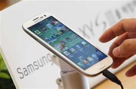 File photo of a man trying Samsung Electronics' new Galaxy S III smartphone that is on display at a store in Seoul