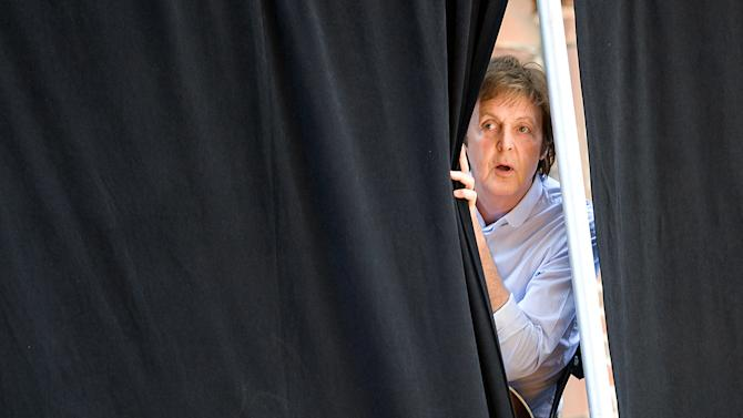 """FILE - In this Wednesday, July 15, 2009 file photo Paul McCartney peeks through the curtains during rehearsals for a performance atop the Ed Sullivan Theater marquee during a taping of """"The Late Show with David Letterman"""" in New York. McCartney turned 70 years of age Monday June 18, 2012. (AP Photo/Charles Sykes)"""