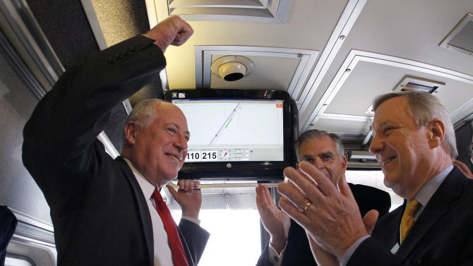 Illinois Gov. Pat Quinn, left, U.S. Transportation Sec. Ray LaHood, center, and US Sen. Dick Durbin, D-Ill., celebrate after the Amtrak train they are riding reached 110 mph during a test run between Dwight and Pontiac, Ill., on Friday, Oct. 19, 2012, in Pontiac, Ill.  (AP Photo/Charles Rex Arbogast)
