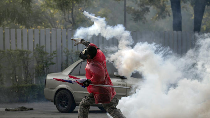 A Thai anti-government protester throws back tear gas canister at riot policemen during a clash at a sport stadium in Bangkok, Thailand Thursday, Dec. 26, 2013. Rock-throwing protesters trying to halt preparations for elections fought police in the Thai capital on Thursday, escalating their campaign to topple the country's beleaguered government. (AP Photo/Wason Wanichakorn)