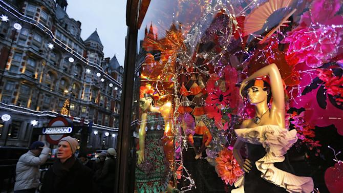"""People walk past a decorated front window of a department store in central London, Thursday, Dec. 20, 2012. Across Europe, holiday """"shoppers"""" this season are doing more browsing than buying. In Rome, some shop for their Christmas presents in sales throughout the year. In Paris, refurbished second-hand toys are attracting buyers. Retailers remain hopeful for a last-minute burst of Christmas consumerism, and some governments are encouraging it by allowing stores to open on Sunday. But with economies across the region slowing and unemployment soaring, analysts say holiday spending in Europe is bound to disappoint for the fourth year in a row. (AP Photo/Lefteris Pitarakis)"""