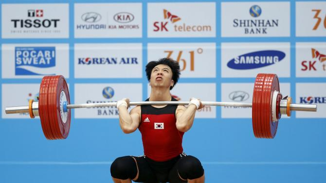 South Korea's Go Suk-kyo attempts a lift in the men's 56kg clean and jerk weightlifting competition at the Moonlight Festival Garden during the 17th Asian Games in Incheon