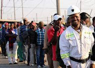 Thousands of Lonmin miners wait in line as they resume work in Marikana after ending a deadly six-week wildcat strike. South African police clashed with residents near an Anglo American mine on Thursday, as miners at nearby Lonmin went back to work