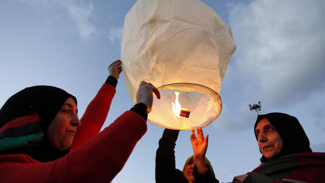 FILE - In this Sunday, Feb. 17, 2013 file photo, Libyans release a lantern in the air at Nasr Square, during the second anniversary of the uprising that toppled longtime dictator Moammar Gadhafi in Benghazi. Women played a major role in the 8-month civil war against dictator Moammar Gadhafi, massing for protests against his regime, selling jewelry to fund rebels, helping treat the wounded, smuggling weapons across enemy lines to rebels. But since Gadhafi's fall more than 18 months ago, women have been rewarded by seeing rights they enjoyed under his rule hemmed in and restricted.  (AP Photo/Mohammad Hannon, File)