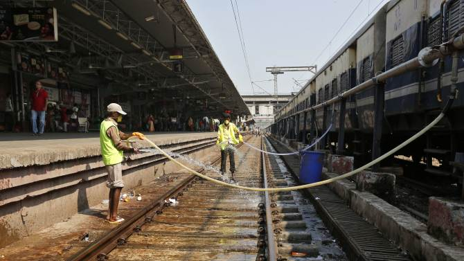 Workers clean a railway track at a railway station in Ahmedabad