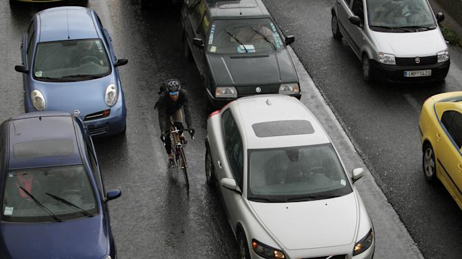 Cars caught in a traffic jam as a cyclist passes among them during a 24-hour strike held by metro, tram and urban railway unions in Athens, Friday, Jan. 18, 2013. Athenians use their cars as workers at Athens metro, tram and urban railway system have walked off the job, striking to protest salary cuts that are part of harsh austerity measures the country is taking to get its hands on bailout cash it needs to avoid bankruptcy. (AP Photo/Thanassis Stavrakis)