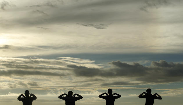 A group of men perform physical exercise training as sun set at Galle Face green in Colombo