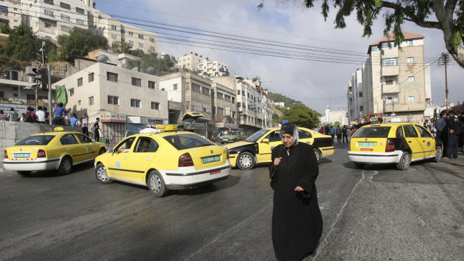 A Palestinian woman walks past parked taxis blocking a road during a protest against the high cost of living in Balata refugee camp in the West Bank city of Nablus, Monday, Sept. 10, 2012. The Palestinian Authority, which governs Palestinians in the West Bank, is suffering a budgetary shortfall because the U.S. and Arab countries that sustain it haven't paid all the aid money that they have promised. (AP Photo/Nasser Ishtayeh)