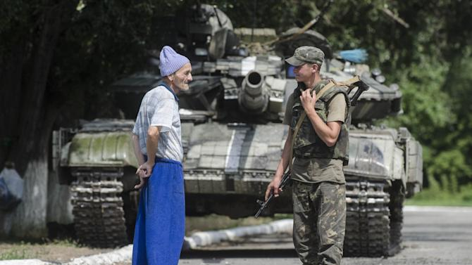 A local citizen speaks to a Ukrainian government soldier guarding a checkpoint outside the city of Siversk, Donetsk region, eastern Ukraine, Saturday, July 12, 2014. Pro-Russian insurgents last week retreated from the strategic city of Slovyansk and holed up in Donetsk, a city of one million, and potentially the final frontier for the rebels. (AP Photo/Evgeniy Maloletka)