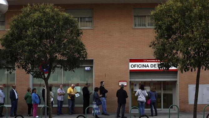 People wait to enter a government-run employment office in Madrid