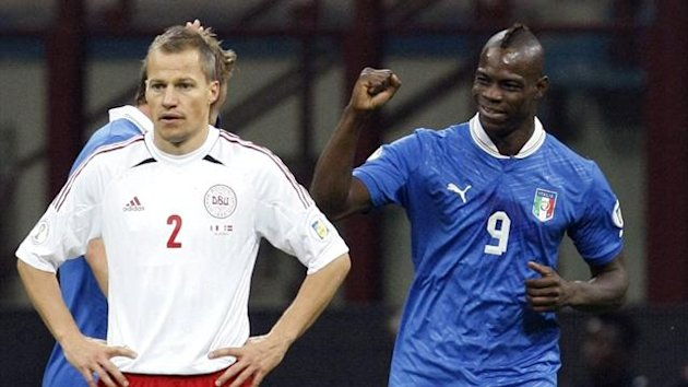 Italy's Mario Balotelli (R) celebrates after scoring their third goal as Denmark's Nicolai Stokholm reacts during their 2014 World Cup qualifying match in Milan