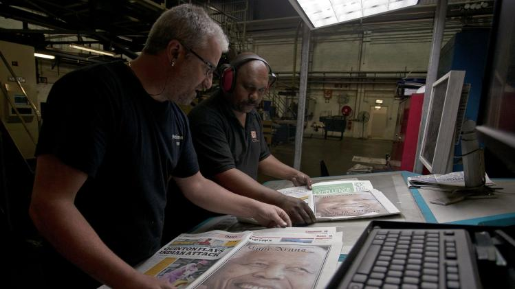 News printers check copies of recently printed newspapers paying tribute to forrmer South Africa's former President Nelson Mandela at a printing press in the early hours of the morning in Cape Town
