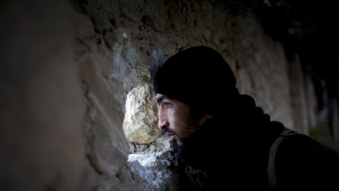A Free Syrian Army fighter scans for Syrian Army positions during an attack on a military academy in Tal Sheer village, north of Aleppo province, Syria, Thursday, Dec. 13, 2012. (AP Photo/Manu Brabo)