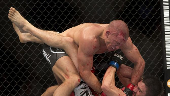 Carlos Condit, bottom, battles with Georges St-Pierre during their UFC welterweight title fight Sunday, November 18, 2012 in Montreal. A relentless St-Pierre celebrated his comeback by winning a five-round decision over Condit to unify the welterweight title in a bloody battle at UFC 154. (AP Photo/The Canadian Press, Ryan Remiorz)