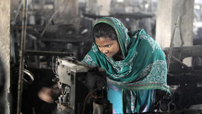 A Bangladeshi garment worker inspects the damaged machinery inside the Smart Export Garment Ltd. factory where a fire Saturday claimed the lives of seven of her female colleagues in Dhaka, Bangladesh, Sunday, Jan. 27, 2013. Bangladesh's government has ordered an investigation into allegations that the sole emergency exit at the factory was locked, an official said Sunday. Saturday's fire occurred just two months after a blaze killed 112 workers in another factory near the capital, raising questions about safety in Bangladesh's garment industry, which exports clothes to leading Western retailers. (AP Photo/A.M. Ahad)