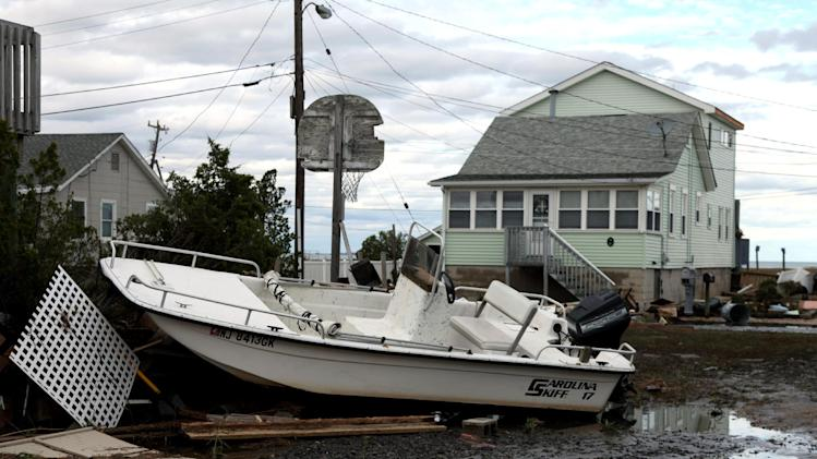 A boat tossed into a neighborhood in the wake of superstorm Sandy on Wednesday, Oct. 31, 2012, in Cedar Bonnet Island, N.J. Power is still out and residents who evacuated the island are still not being allowed back in. Sandy is considered responsible for at least six deaths across the state of New Jersey in addition to power outages. (AP Photo/Robert Ray)