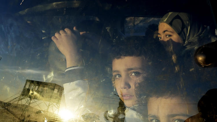 Syrian children look through their car window as they cross into Lebanon with their families at the border crossing, in Masnaa, eastern Lebanon, Friday, Nov. 30, 2012. (AP Photo/Hassan Ammar)