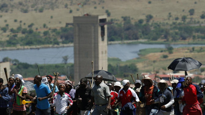 In this photo taken Thursday Oct. 18 2012, showing miners as they sing and march during their strike at the AngloGold Ashanti Mine, in Fochville near Johannesburg, South Africa.  It is widely reported Thursday Oct. 25, 2012, that an ultimatum from mining companies to striking mineworkers appears to be getting the desired result, forcing thousands to settle for less than their original demands as they scramble to save their jobs. (AP Photo/Themba Hadebe-file)
