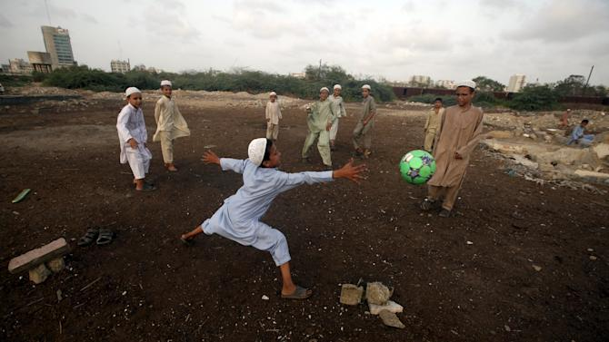 Madrasa students play soccer on the grounds of a slum in Karachi