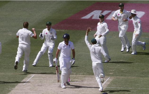 Australia's team celebrates after taking the wicket of England's captain Alastair Cook during the second day of the fifth Ashes cricket test at the Sydney cricket ground