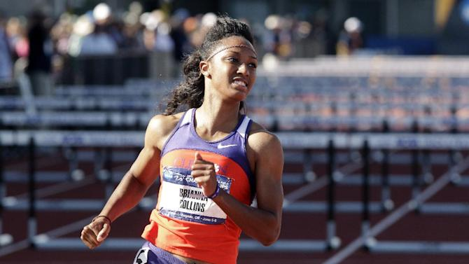 Clemson's Brianna Rollins looks at the scoreboard for her time after winning her heat in the 100-meter hurdles preliminary race during the NCAA Track and Field Championships in Eugene, Ore., Thursday, June 6, 2013. Rollins set a new American collegiate record. (AP Photo/Don Ryan)