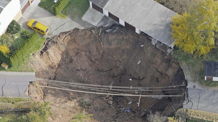 In this aerial photo, a giant landslide under a residential street is seen in Schmalkalden, central Germany, Monday, Nov. 1, 2010. The cause of the landslide is yet unclear unclear. Residents were evacuated from 23 buildings. Nobody was injured. (AP Photo/Jens Meyer)