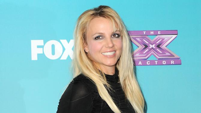 """FILE - This Nov. 5, 2012 file photo shows singer and celebrity judge Britney Spears at the """"X-Factor"""" Finalists Party in Los Angeles. A person familiar with plans for Fox's """"The X Factor"""" says Britney Spears is out of the show. Spears was a mentor on the singing contest for one season, reportedly drawing a $15 million paycheck but failing to pull reviews to match. The person who confirmed reports of her departure wasn't authorized to comment publicly, speaking Thursday on condition of anonymity. (Photo by Jordan Strauss/Invision/AP, file)"""