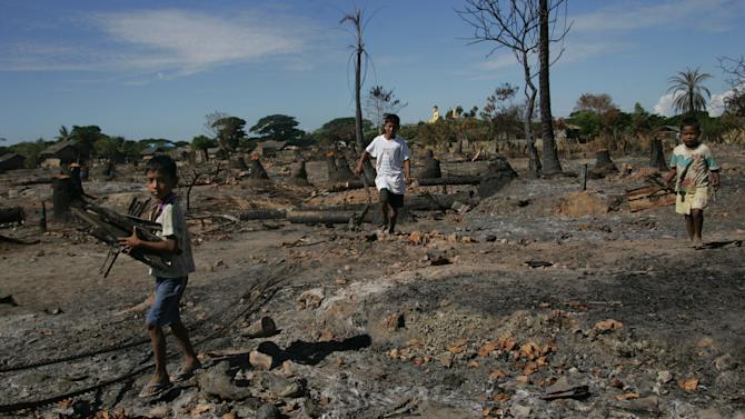 In this photo taken on Nov. 7, 2012, children carry half-burned wood, debris of burnet down buildings following recent violence, in Pauk Taw, Rakhine state, western Myanmar. The Oct. 24 exodus was part of a wave of violence that has shaken western Myanmar twice in the last six months. But what began with a series of skirmishes that pitted ethnic Rakhine Buddhists against Rohingya, a Muslim minority, appears to have evolved into something far more disturbing: a region-wide effort by Buddhists to drive Muslims out with such ferocious shows of hatred that they could never return. (AP Photo/Khin Maung Win)