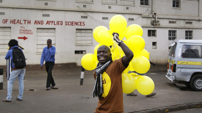"A volunteer carries a bunch of yellow balloons to hand out to commuters as part of an art project by American artist Yazmany Arboleda in Nairobi, Kenya Monday, Nov. 7, 2011. Thousands of yellow balloons are floating above commuters in downtown Nairobi, igniting smiles among Kenyans wary of bomb warnings after two recent grenade attacks, in the third in a series of seven art projects around the world known as ""Monday Morning."" (AP Photo/Khalil Senosi)"