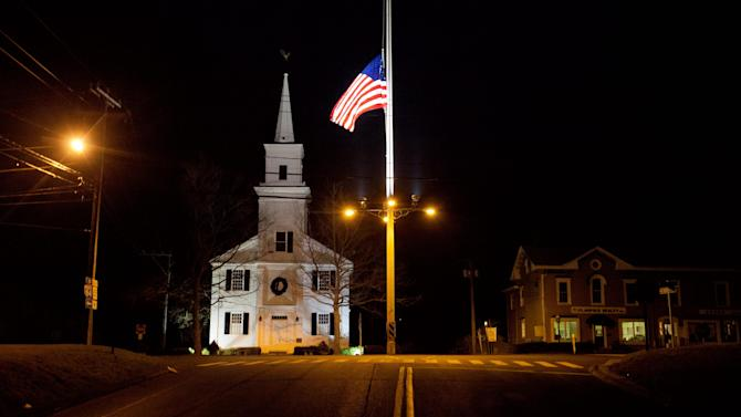 FILE - A U.S. flag flies at half-staff on Main Street in Newtown, Conn. on Saturday, Dec. 15, 2012 in honor of those killed when a gunman opened fire inside the town's Sandy Hook elementary school. In just a four-month span, New England has been the backdrop for two incidents of mass carnage - the Dec. 14, 2012 shootings in Newtown, that killed 20 children and six staff members at the school, and the Boston Marathon bombings on April 15, 2013 that killed three people and injured more than 260. (AP Photo/David Goldman, File)