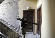 A Free Syrian Army fighter watches Syrian Army positions before firing a B-10 recoilless gun in the Haresta neighbourhood of Damascus in this February 7, 2013 file photograph. REUTERS/Goran Tomasevic/Files