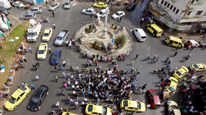 Palestinian taxis drive around a main square in the West Bank city of Ramallah in protest against the high cost of living in the West Bank, Monday, Sept. 10, 2012. Palestinian demonstrators fed up with high prices and unpaid salaries shuttered shops, halted traffic with burning tires and closed schools throughout the West Bank on Monday in the largest show of popular discontent with the governing Palestinian Authority in its 18-year history. (AP Photo/Majdi Mohammed)