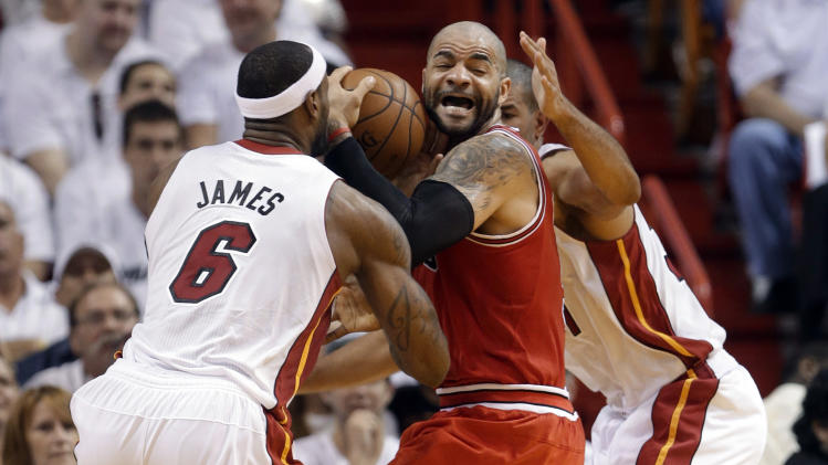 Chicago Bulls' Carlos Boozer, center, works the ball between Miami Heat's LeBron James (6) and Shane Battier, right, as he attempts to shoot during the first half of Game 5 of an NBA basketball Eastern Conference semifinal, Wednesday, May 15, 2013, in Miami. (AP Photo/Wilfredo Lee)