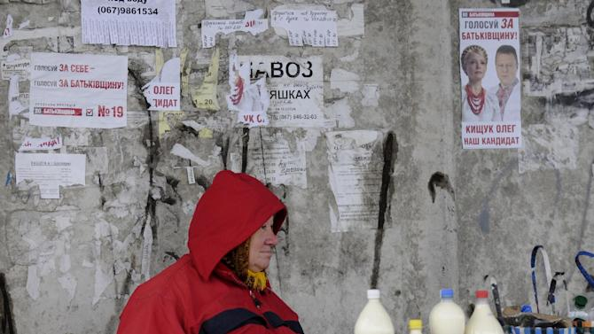 A woman selling milk at the market in the village of Bobryk, some 60 km (37 miles) north of Kiev Ukraine, Saturday, Oct. 27, 2012.  Ukraine is scheduled to hold parliamentary elections on Oct. 28. (AP Photo/Sergei Chuzavkov)