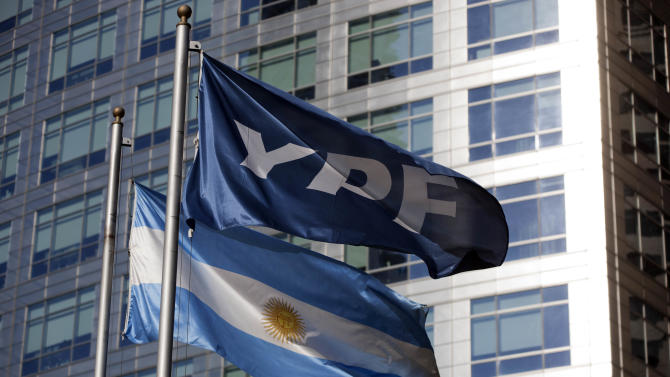 FILE - In this April 16, 2012 file photo, an Argentine national flag and a banner representing the YPF oil company flutter outside YPF headquarters in Buenos Aires, Argentina. Argentina's government said Monday, Nov 25, 2013, it has reached an agreement in principle to compensate Spain's Repsol for last year's 51 percent expropriation of the energy company. (AP Photo/Natacha Pisarenko, File)