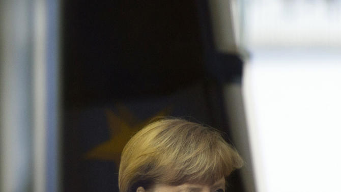 German Chancellor Angela Merkel walks through the lobby of the Chancellery to welcome French President Francois Hollande and French Prime Minister Jean-Marc Ayrault, unseen, in Berlin, Germany, Tuesday, Jan. 22, 2013. France and Germany mark 50 years since they signed the Elysee Treaty, the post-war friendship pact between the former enemies. (AP Photo/Gero Breloer)