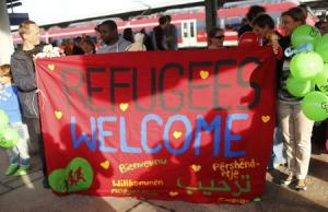 People hold a welcome banner as they wait for migrants…