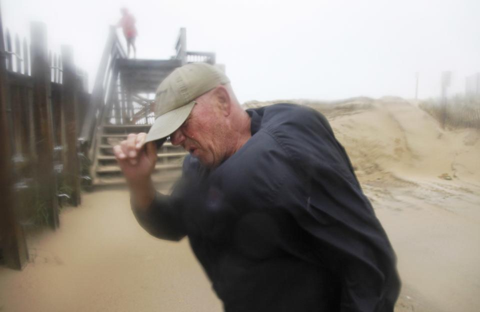 Summer resident Jody Bowers braces himself from a blast of sand and driving rain as he makes his way to the beach in Kill Devil Hills, N.C., Saturday, Aug. 27, 2011 as Hurricane Irene reaches the North Carolina coast. (AP Photo/Charles Dharapak)
