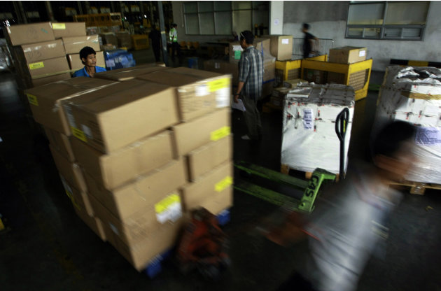 In this photo taken July 17, 2012, workers push boxes of shipment through custom office at Suvarnabhumi International Airport in Bangkok, Thailand. Officials at Thailand's gateway airport proudly tick