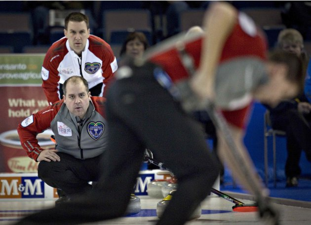 Newfoundland skip Gushue watches from behind Northwest Territories skip Koe during play at the Canadian Men's Curling Championships in Edmonton