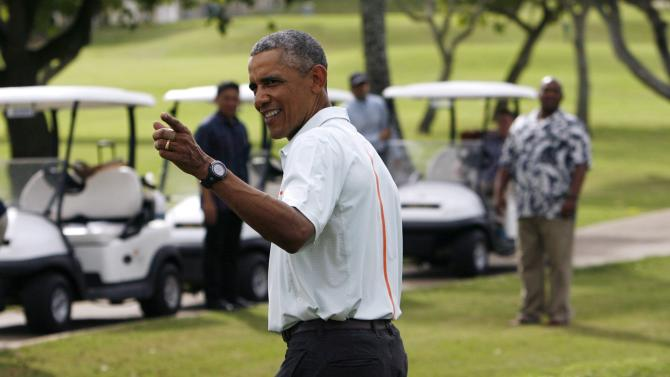U.S. President Barack Obama gestures to the media after he and Malaysia's Prime Minister Najib Razak played on the 18th green in Kaneohe