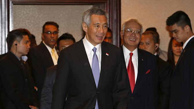 Singapore's Prime Minister Lee Hsien Loong arrives with Malaysian counterpart Najib Razak for a news conference after a meeting in Singapore