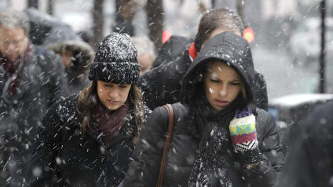 Commuters brace the snow as they arrive in downtown Chicago Tuesday, March 5, 2013. Chicago was hit Tuesday by a storm expected to dump as much as 10 inches of snow in the area before the end of the day — the most since the 2011 blizzard and its more than 20 inches of snow. (AP Photo/Kiichiro Sato)