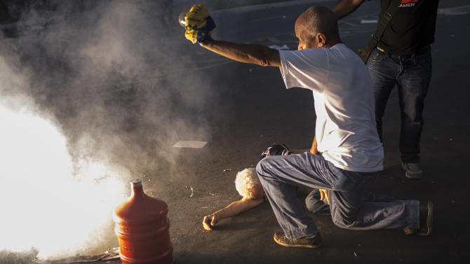 A sound grenade explodes next to a man who was already laying on the ground injured during a protest outside the Minerao stadium during a match between Japan and Mexico in Belo Horizonte, Brazil, Saturday, June 22, 2013. Thousands of anti-government demonstrators again took to streets in several Brazilian cities Saturday after the president broke a long silence to promise reforms.(AP Photo/Felipe Dana)