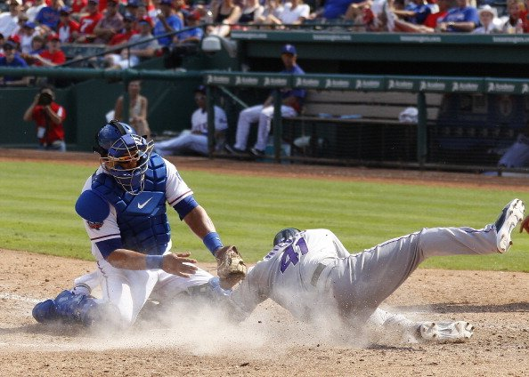Yorvit Torrealba #8 of the Texas Rangers tags Wil Nieves #41 of the Colorado Rockies out at home in the interleague game at Rangers Ballpark in Arlington on June 23, 2012 in Arlington, Texas. (Photo b