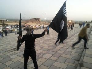 A fighter of the ISIL holds a flag and a weapon on…