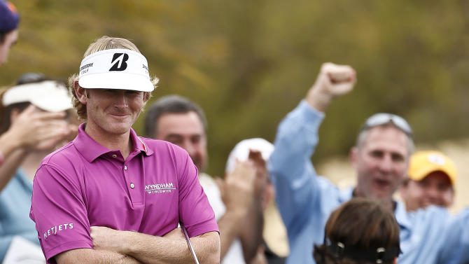 Brandt Snedeker, left, smiles as Phil Mickelson walks past after Mickelson madea long birdie putt on the seventh hole during the final round of the Waste Management Phoenix Open golf tournament on Sunday, Feb. 3, 2013, in Scottsdale, Ariz. (AP Photo/Ross D. Franklin)