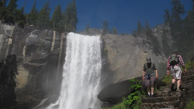 FILE - In this July 20, 2011 file photo, Hikers walk on the Mist Trail to Vernal Fall in Yosemite, Calif. Visitors to America's national parks will encounter fewer rangers, find locked restrooms and visitors centers, and see trash cans emptied less often if 5 percent across-the-board cuts are enacted by sequestration. A National Park Service internal memo obtained by The Associated Press compiles a list of cuts in services in parks from Cape Cod to Yosemite. It's the result of an order by Park Service Director John Jarvis in January that asked superintendents to show how they will absorb the funding cuts.  (AP Photo/Gosia Wozniacka)